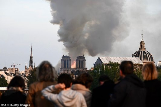 12311216-6927101-parisians_and_toursits_look_on_in_utter_shock_as_the_flames_engu-a-12_1555403983198